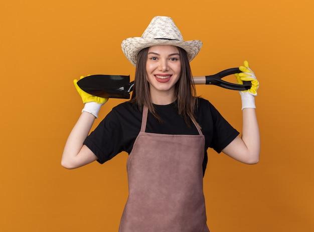 뒤에 목에 삽을 들고 원예 모자와 장갑을 끼고 예쁜 백인 여성 정원사 미소