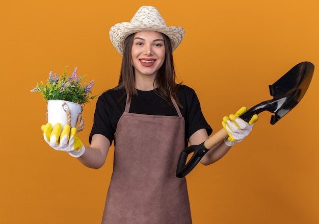 Sorridente giardiniere femmina caucasica che indossa cappello e guanti da giardinaggio tiene vaso di fiori e vanga isolati sulla parete arancione con spazio di copia