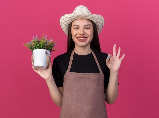 화분을 들고 분홍색에 확인 표시를 몸짓으로 원예 모자를 쓰고 웃는 예쁜 백인 여성 정원사