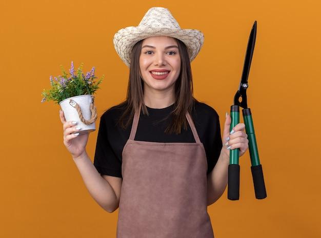 Giardiniere femminile abbastanza caucasico sorridente che porta il cappello di giardinaggio che tiene il vaso di fiori e le forbici di giardinaggio isolate sulla parete arancio con lo spazio della copia