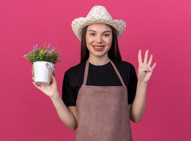 Giardiniere femminile abbastanza caucasico sorridente che porta il cappello di giardinaggio che tiene il vaso di fiori e che gesturing quattro con le dita isolate sulla parete rosa con lo spazio della copia