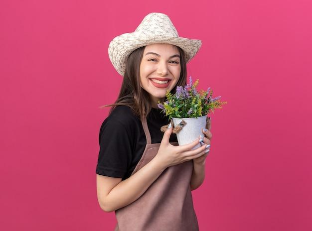 Sorridente giardiniere femmina caucasica che indossa cappello da giardinaggio con fiori in vaso di fiori isolato su parete rosa con spazio di copia