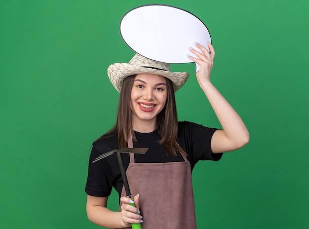 복사 공간이 있는 녹색 벽에 격리된 괭이 갈퀴와 말풍선을 들고 있는 원예용 모자를 쓰고 웃고 있는 백인 여성 정원사