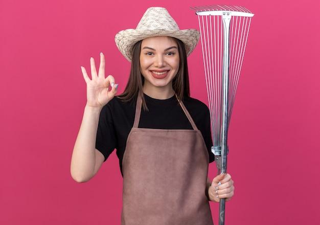 잎 갈퀴를 들고 ok 사인을 몸짓으로 원예 모자를 쓰고 웃는 예쁜 백인 여성 정원사