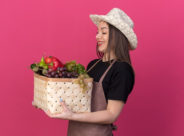 Smiling pretty caucasian female gardener wearing gardening hat holding and looking at vegetable basket isolated on pink wall with copy space