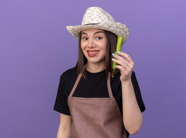 コピースペースと紫色の壁に分離された壊れた唐辛子の一部を保持している園芸帽子を身に着けているかなり白人女性の庭師の笑顔