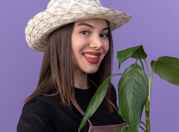 Улыбающаяся красивая кавказская женщина-садовник в садовой шляпе держит ветку растения и изолирована на фиолетовой стене с копией пространства