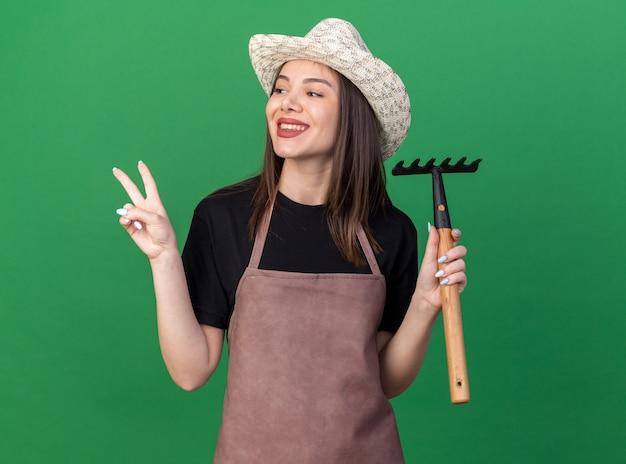 Улыбающаяся красивая кавказская женщина-садовник в садовой шляпе держит грабли и жестикулирует знак победы, глядя в сторону