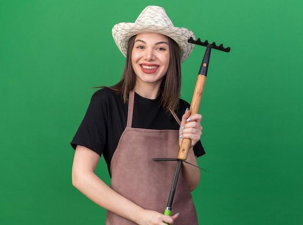 コピースペースと緑の壁に分離されたくわ熊手の上に熊手を保持しているガーデニング帽子をかぶっているかなり白人女性の庭師の笑顔