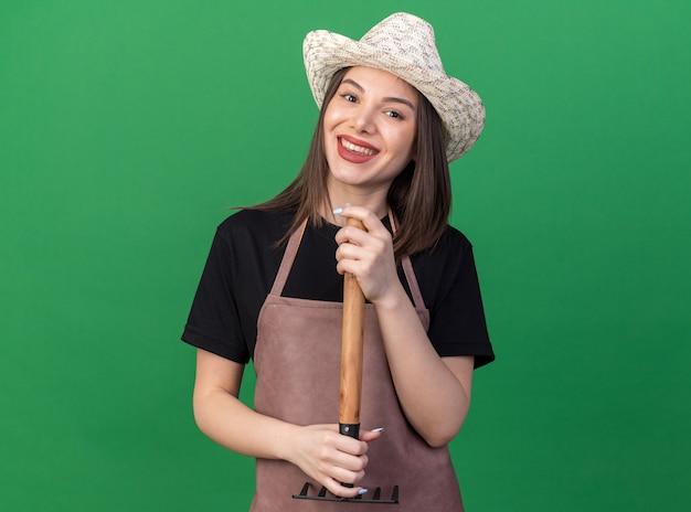 복사 공간이 있는 녹색 벽에 거꾸로 갈퀴를 들고 있는 원예용 모자를 쓰고 웃고 있는 백인 여성 정원사
