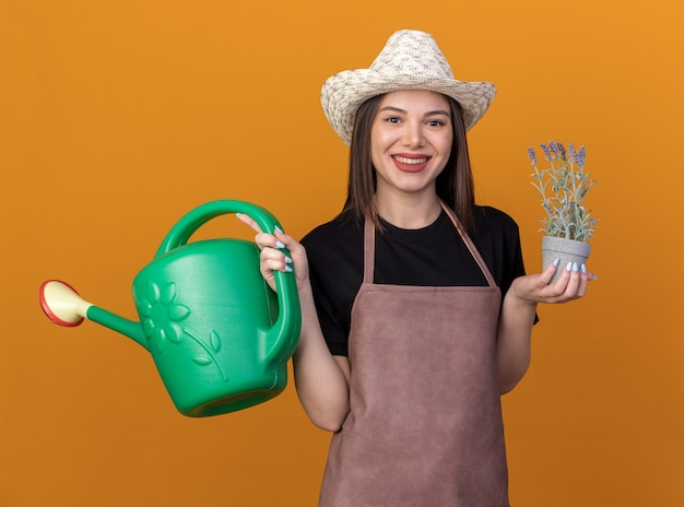 Smiling pretty caucasian female gardener wearing gardening hat holding watering can and flowerpot on orange