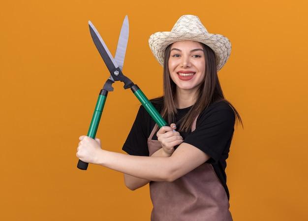 Улыбающаяся красивая кавказская женщина-садовник в садовой шляпе держит садовые ножницы, изолированные на оранжевой стене с копией пространства