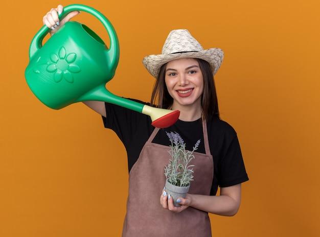 Sorridente giardiniere femminile abbastanza caucasico che indossa cappello da giardinaggio che finge di innaffiare i fiori in vaso di fiori con annaffiatoio isolato sulla parete arancione con spazio di copia
