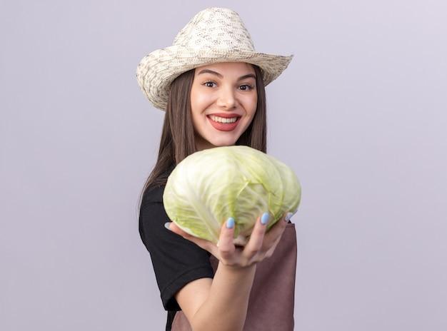Улыбающаяся красивая кавказская женщина-садовник в садовой шляпе стоит боком, держа капусту
