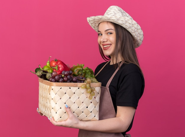 Sorridente giardiniere femmina caucasica che indossa un cappello da giardinaggio si erge lateralmente tenendo un cesto di verdure isolato sulla parete rosa con spazio di copia