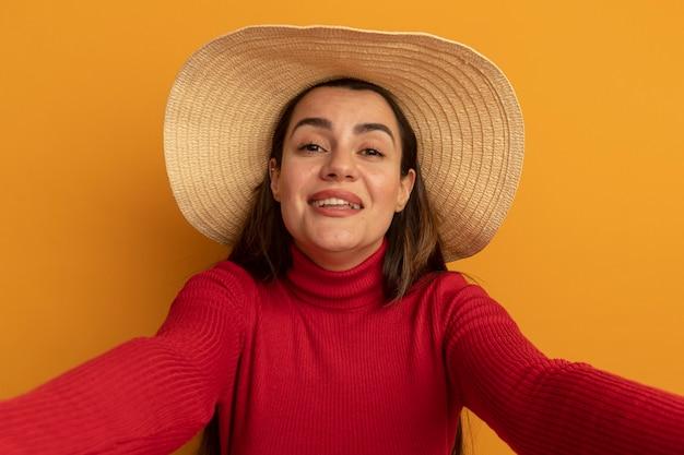 La donna abbastanza caucasica sorridente con il cappello della spiaggia finge di tenere la fotocamera sull'arancio