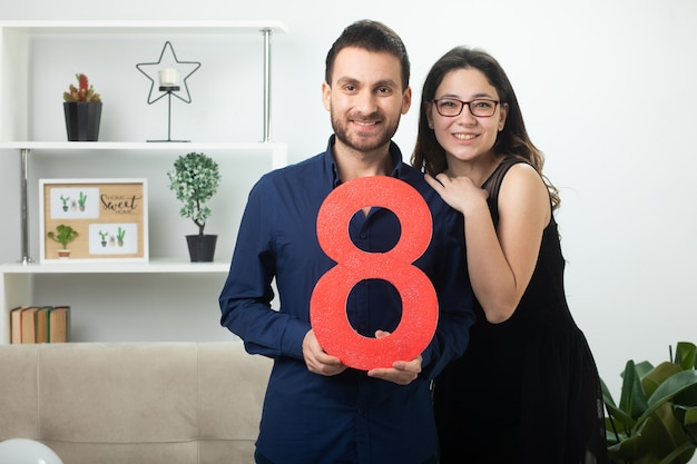 Smiling pretty couple holding red eight figure standing in living room on march international women's day