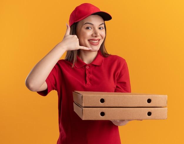 Улыбающаяся красивая женщина-доставщик в единообразных жестах зовет меня знаком рукой и держит коробки для пиццы, изолированные на оранжевой стене с копией пространства