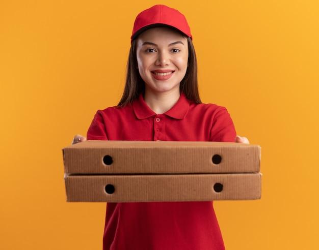 Улыбающаяся красивая женщина-доставщик в униформе протягивает коробки для пиццы, изолированные на оранжевой стене с копией пространства