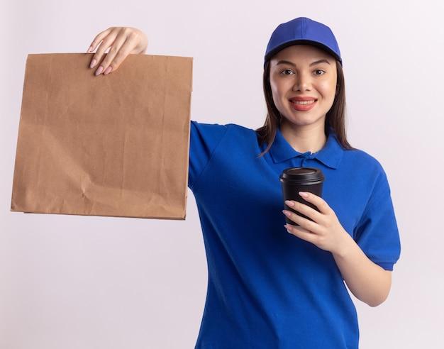 제복을 입은 예쁜 배달 여자가 흰색에 카메라를보고 종이 패키지와 종이 컵을 보유하고있다.
