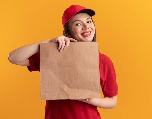 制服を着た笑顔のかわいい配達の女性は、コピースペースでオレンジ色の壁に分離された紙のパッケージを保持します