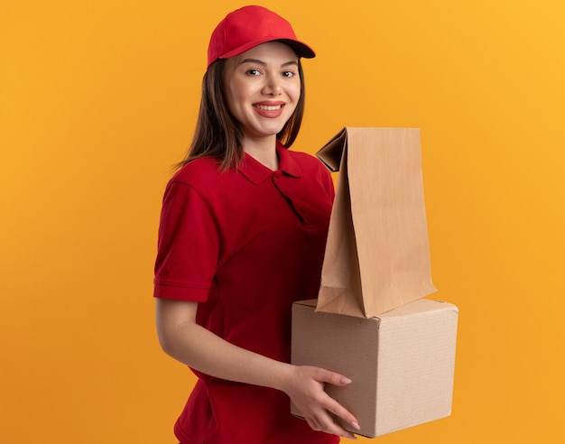 제복을 입은 웃고 있는 예쁜 배달 여성은 복사 공간이 있는 주황색 벽에 격리된 카드박스에 종이 패키지를 들고 있습니다