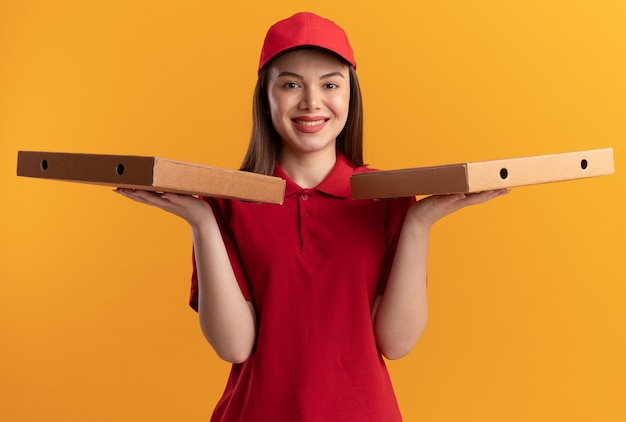 제복을 입은 예쁜 배달 여자 미소는 오렌지에 손에 피자 상자를 보유