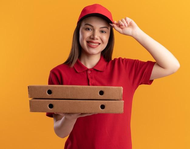 제복을 입은 예쁜 배달 여자가 모자에 손을 대고 오렌지에 피자 상자를 보유하고 있습니다.