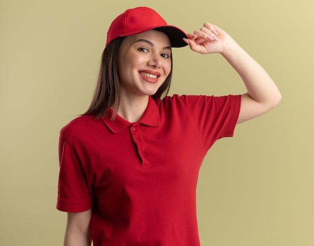 制服を着た笑顔のかわいい配達の女性は、コピースペースでオリーブグリーンの壁に分離されたキャップに手を置きます