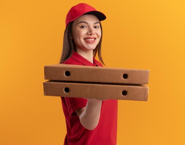 제복을 입은 예쁜 배달 여자 미소 옆으로 오렌지에 피자 상자를 들고 서