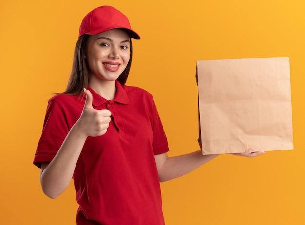 제복을 입은 예쁜 배달부 여성이 엄지손가락을 치켜들고 주황색 벽에 복사 공간이 있는 종이 패키지를 들고 있습니다.