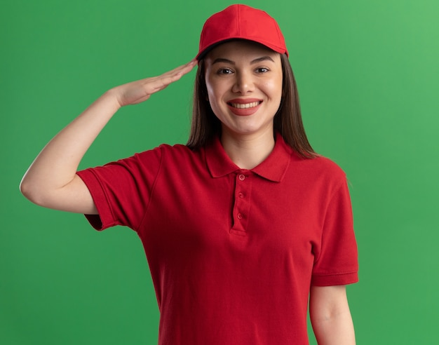 Smiling pretty delivery woman in uniform doing salute gesture