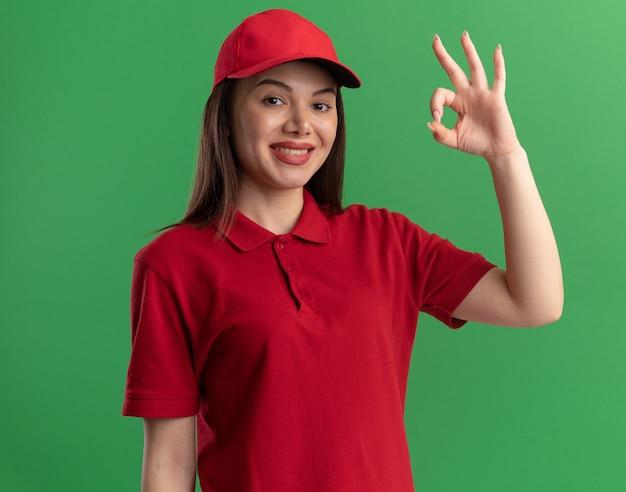 Sorridente bella donna di consegna in gesti uniformi segno di mano ok isolato sulla parete verde con spazio di copia