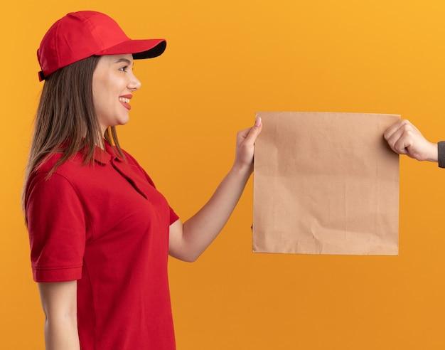 La donna sorridente graziosa delle consegne in uniforme dà il pacchetto di carta a qualcuno isolato sulla parete arancione con lo spazio della copia