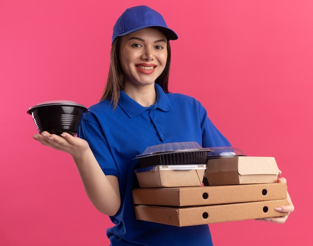 Smiling pretty delivery woman in uniform holding food package and containers on pizza boxes isolated on pink wall with copy space