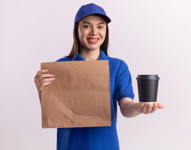 Sorridente donna graziosa di consegna in uniforme che tiene pacchetto di carta e bicchiere di carta isolato sulla parete bianca con lo spazio della copia