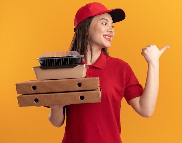 La graziosa donna delle consegne sorridente in uniforme tiene in mano confezioni di cibo di carta su scatole per pizza guardando e indicando di lato