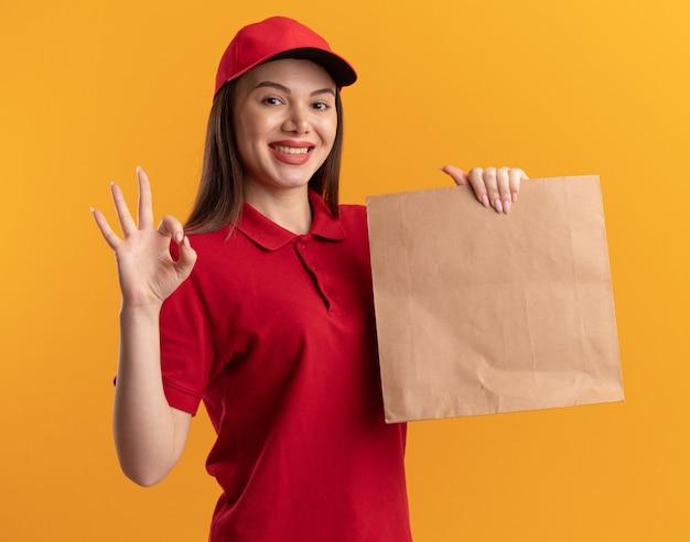 La donna graziosa sorridente di consegna in uniforme tiene il pacchetto di carta e gesti il segno giusto della mano sull'arancia