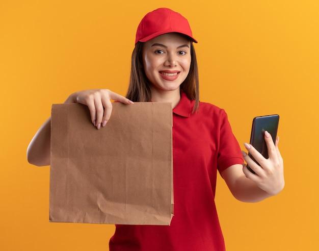 La donna graziosa sorridente di consegna in uniforme tiene il pacchetto di carta e il telefono sull'arancio