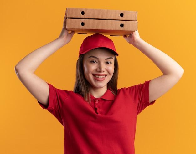 La donna graziosa sorridente di consegna in uniforme tiene le scatole della pizza sopra la testa sull'arancia