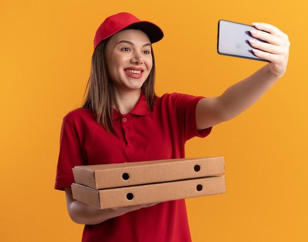 La graziosa donna delle consegne sorridente in uniforme tiene in mano scatole di pizza e guarda il telefono facendo selfie