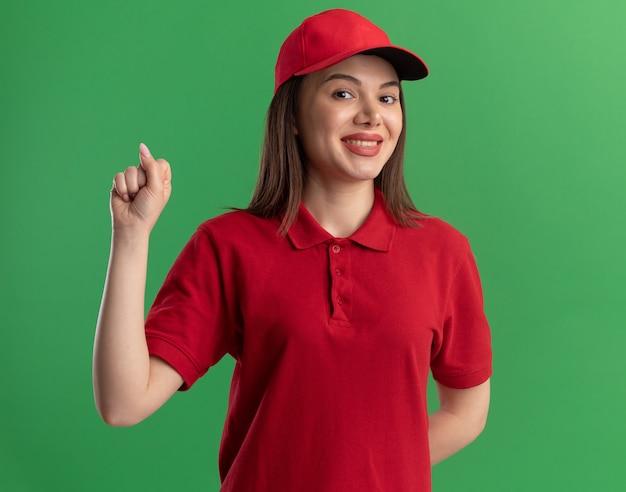 Sorridente bella donna di consegna in uniforme che tiene il pugno isolato sulla parete verde con spazio di copia