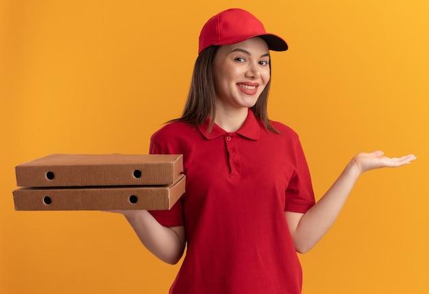 La donna sorridente graziosa delle consegne in uniforme tiene la mano aperta e tiene le scatole della pizza isolate sulla parete arancione con lo spazio della copia