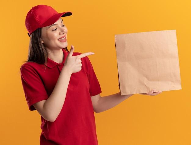 Sorridente bella donna delle consegne in uniforme guarda e indica il pacchetto di carta isolato sulla parete arancione con spazio di copia