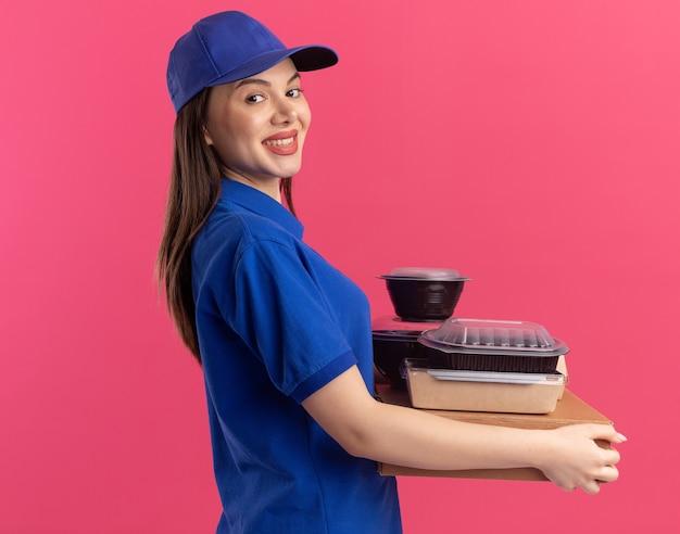 La graziosa donna delle consegne sorridente in uniforme sta in piedi lateralmente tenendo il pacchetto di cibo e i contenitori su scatole per pizza