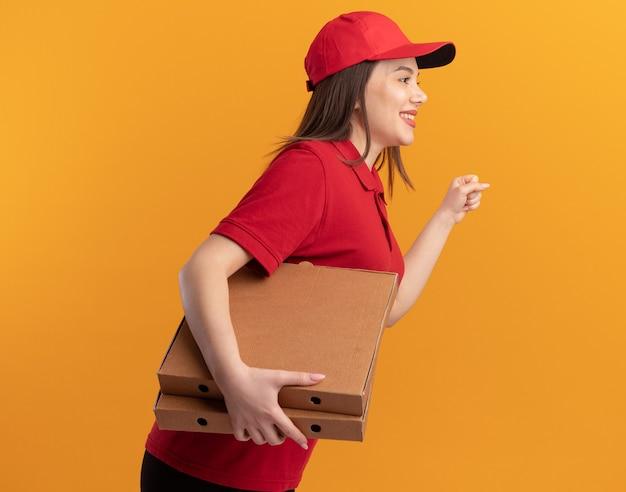 Sorridente bella donna delle consegne in uniforme sta di lato tenendo scatole per pizza e tenendo il pugno isolato sulla parete arancione con spazio di copia