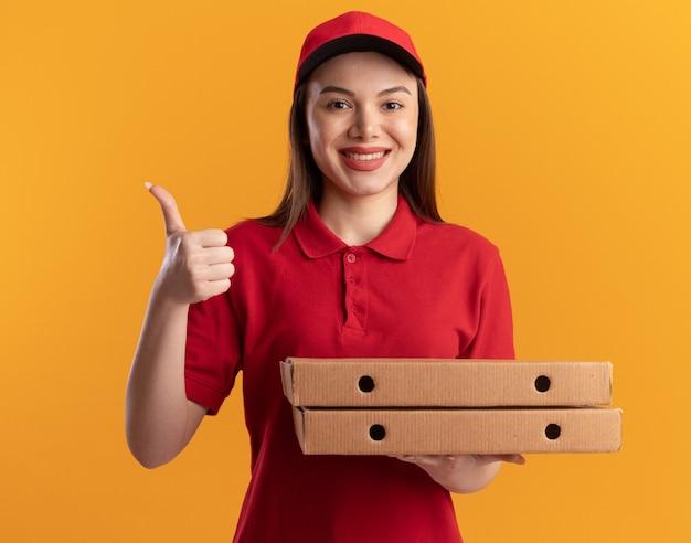 Sorridente bella donna delle consegne in uniforme pollice in alto e tiene scatole per pizza