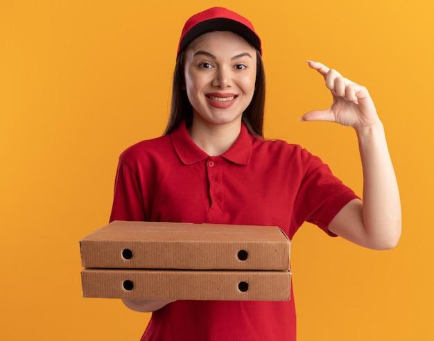 La graziosa donna delle consegne sorridente in uniforme con scatole per pizza finge di tenere qualcosa