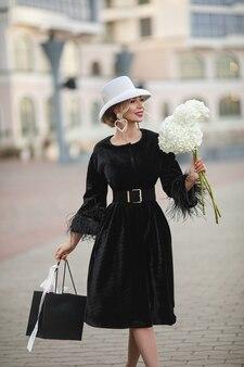 通りを歩いている白い帽子と黒いドレスを着たかなりエレガントな女性の笑顔。ファッションストリートのコンセプト