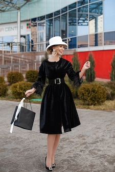 Smiling pretty elegant lady in white hat and black dress walking on the street. fashion street concept
